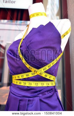 Tailors purple textile dress dummy with measure tape.