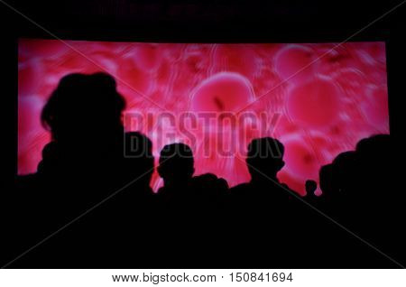 Unrecognizable people in a black and pink trance dance party.