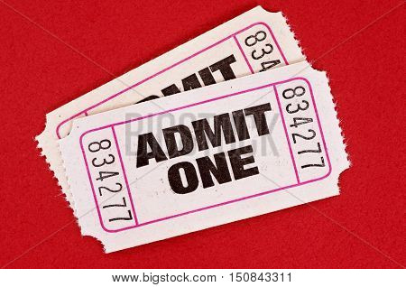 Two white admit one movie tickets on a red background.