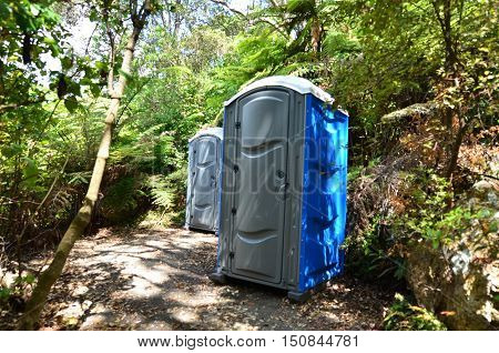 Many portable grey and blue outdoor Toilets in the woods.