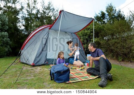 Young family father and mother with two children camping in a tent outdoors.