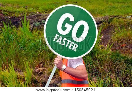 Unrecognizable Road Worker Holds Go Faster Traffic Road Signpost