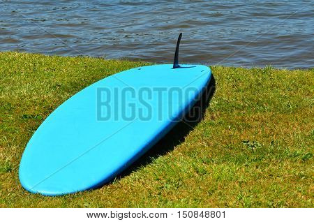 Blue Standup Paddle Board On River Bank