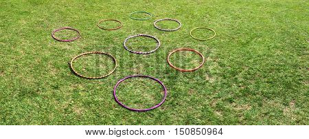 Nine 9 hula hoops on a green grass. Abstract background with copy space.