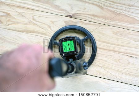 Mans Hand Searching Metal With Metal Detector