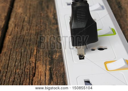 white plug socket electric power bar or extension block Select focus with shallow depth of fieldand one plugged in power cord on wooden table background and copy space