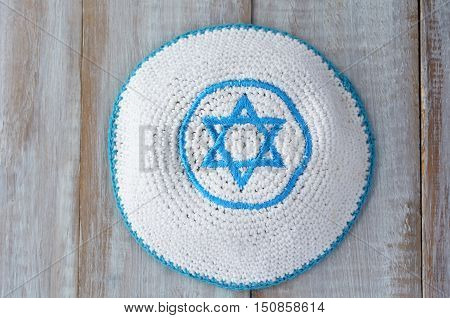 Flat Lay Of A Knitted Kippah With Embroidered Blue And White Star Of David