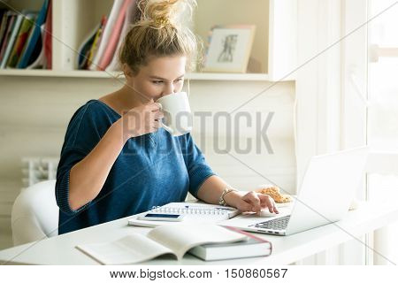 Portrait of young beautiful smiling casual woman sitting at office desk enjoying her cup of coffee while working or studying on laptop computer at small home office or in the student dorm. Indoors