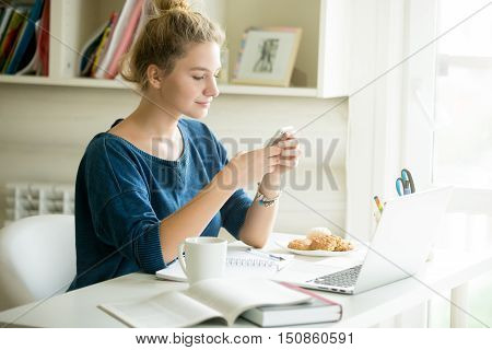 Portrait of young beautiful casual woman holding smartphone, looking at screen, using app or messaging while sitting at modern workplace with laptop, books, coffee and cookies in home office or dorm