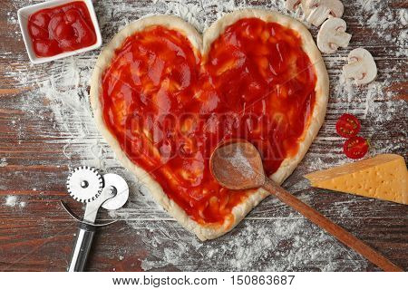 Pizza dough in heart shape covered with tomato sauce on table