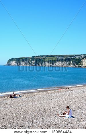SEATON, UNITED KINGDOM - JULY 18, 2016 - View of the pebble beach and coastline with holidaymakers enjoying the setting Seaton Devon England UK Western Europe, July 18, 2016.
