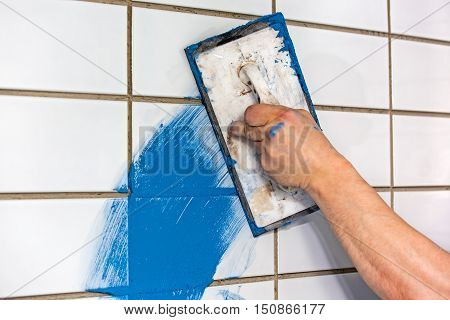 Builder Applying Colorful Blue Grouting