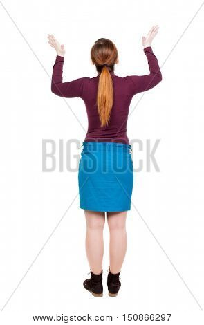 Back view of Beautiful woman in jeans looking at wall and Holds  hand up.  young blonde girl standing. Rear view people. Isolated over white background. Young woman in prayer