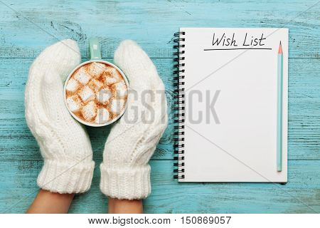 Woman hands in mittens hold cup of hot cocoa or chocolate with marshmallow and notebook with wish list on turquoise vintage table from above, christmas planning concept. Flat lay style. poster
