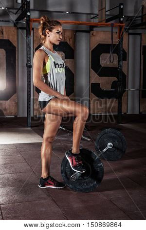 Young woman with a perfect body is preparing for the exercises with barbell in gym