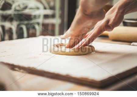 Hands preparing dough basis for pizza on the wooden table close-up