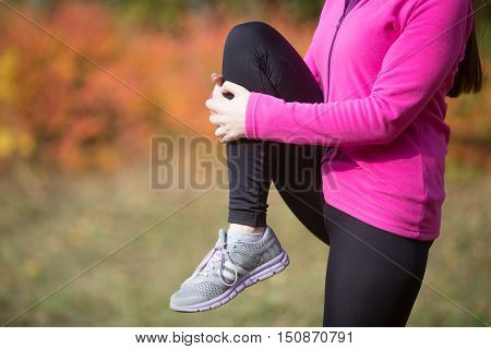 Warming up outdoors in the fall, holding a leg, stretching after or before running. Concept photo