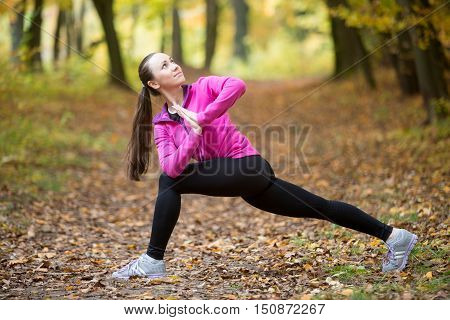 Sporty beautiful young woman practicing yoga, standing in Revolved Side Angle Posture, Parivrtta Parsvakonasana, working out outdoor on autumn day wearing sportswear sweatshirt. Full length, side view