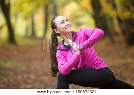 Sporty beautiful happy young woman practicing yoga, standing in Revolved Side Angle Posture, Parivrtta Parsvakonasana, working out outdoor on autumn day wearing sportswear sweatshirt. Closeup portrait