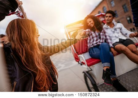 Young people enjoying tricycle ride in the city. Teenagers riding on tricycle on road with woman holding hand of female friend.