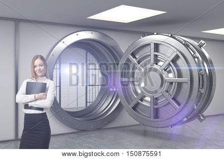 Blond woman with folder is standing near open bank vault and looking at the viewer. Concept of bank employee. Toned image