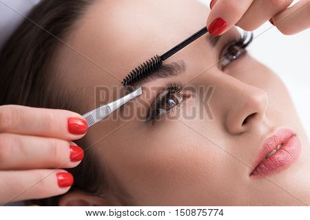 Close up of cosmetician hands pulling out female eyebrows by tweezers and combing it by brush. Young woman is looking forward with tranquility