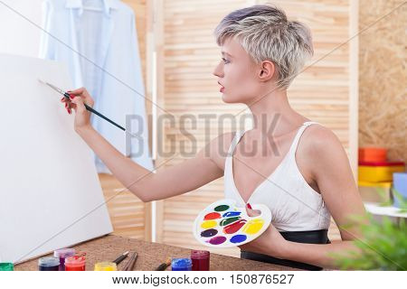 Beautiful woman painter is drawing her picture using an easel and a palette. Concept of depicting nature