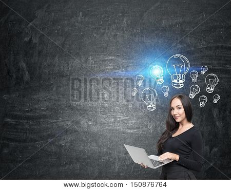 Girl with laptop standing near blackboard with blue shining light bulb. Concept of bright person. Mock up