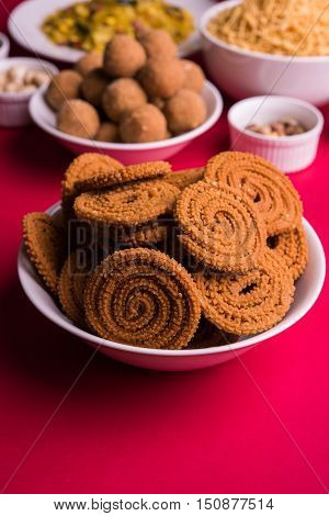 home made tasty Diwali food or Diwali snacks or Diwali sweets like rava laddu, chakli, sev,shankar pale and chivda or chiwada with dry fruits in white bowls, favourite indian diwali recipe
