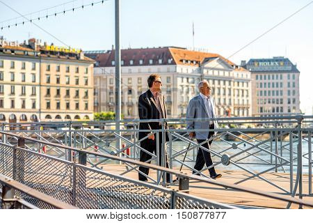 Geneva, Switzerland - June 23, 2016: Elder businessmen walk on the pedestrian bridge in the center of Geneva city. Geneva is a financial center and worldwide center for diplomacy in Europe