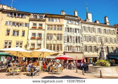 Geneva, Switzerland - June 23, 2016: Bourg-de-four square with people sit in cafes and restaurants. It is the oldest square and the most popular meeting place in Geneva.