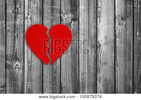 Broken heart on black and white wooden background