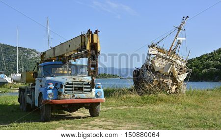 An old abandoned truck with a winch and a derelict beached ship outside the Croatian village of Blace.