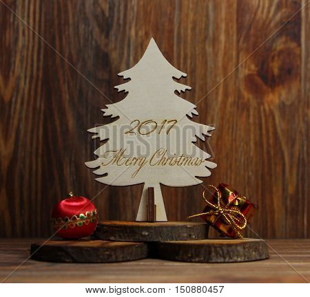 Christmas tree on a stub with a Christmas tree decoration, a gift on a wooden background