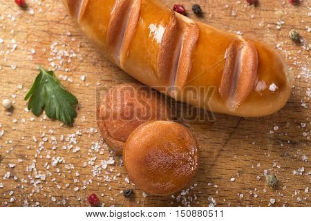 Fried Polish sausage and two slices on an wooden board with herbs
