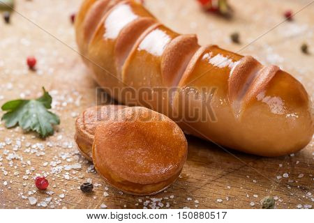Two slices of Polish sausage on an wooden board with herbs