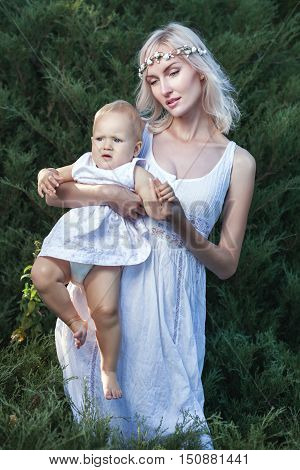 The girl in a white dress holding a baby in her arms.