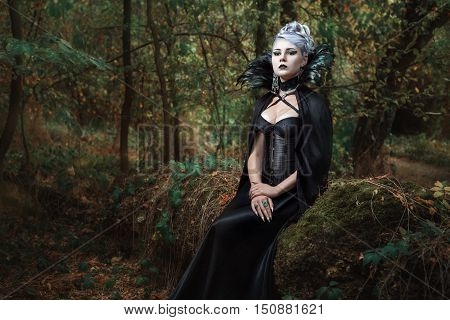 Gothic girl in black raincoat sits on a tree in the forest.