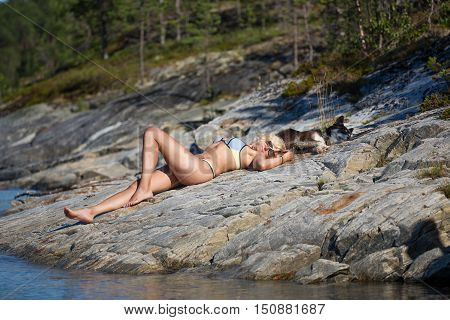 Beautiful woman with her cute dog is laying on the stone beach near of the White sea