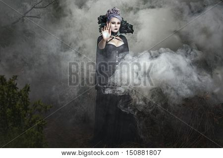 Gothic girl in black clothes stands in the smoke.