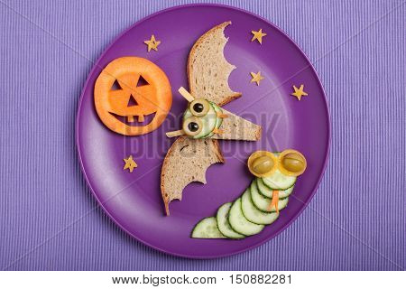 Halloween bat and snake made of bread and cucumber on plate and fabric