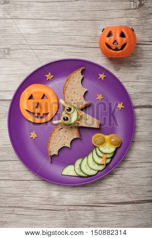 Halloween bat and snake made of bread and cucumber on plate and board