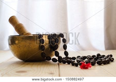 Closeup of a tibetan bowl and mala beads for meditation on wood background
