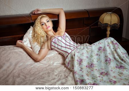 Glamorous woman in a dress lying on the bed.