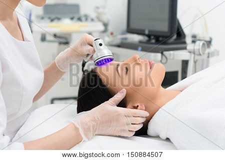 Relaxed young woman is enjoying laser facial massage at medical cosmetology spa salon. She is lying and resting poster