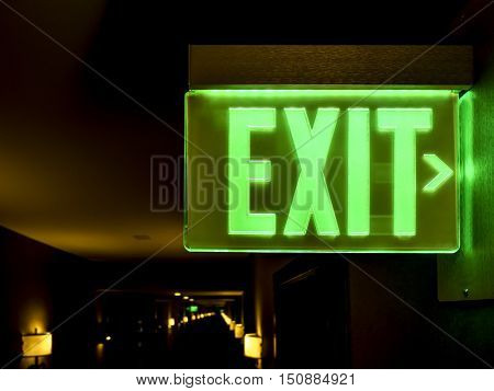 Close-up view of an illuminated green exit sign in a hotel