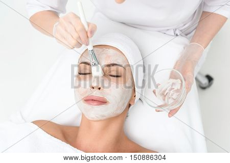Top view close-up of cosmetologist arms applying cream on female face. She is holding brush and bowl. Young woman is lying and resting. Her eyes are closed with pleasure