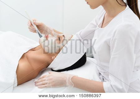 Professional beautician is applying healthy cream on female facial skin with concentration. Serene young woman is lying on table and enjoying treatment