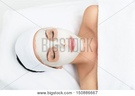Tranquil young woman is enjoying skin care treatment at beauty salon. She is lying with clay mask over her face. Her eyes are closed with harmony