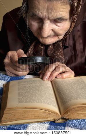 Elderly woman reading Bible with magnify glass